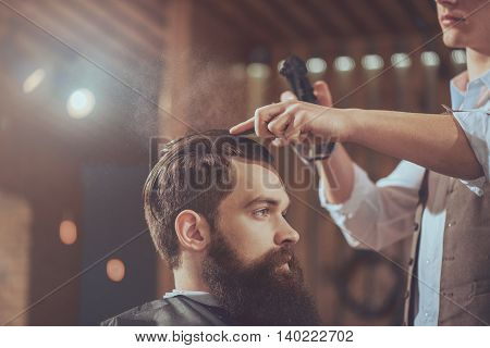 Satisfied customer. Cropped image of male barber cutting hair with a comb being in a barber shop