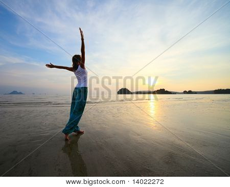 Young woman with raised hands standing on wet sand and looking to a sky