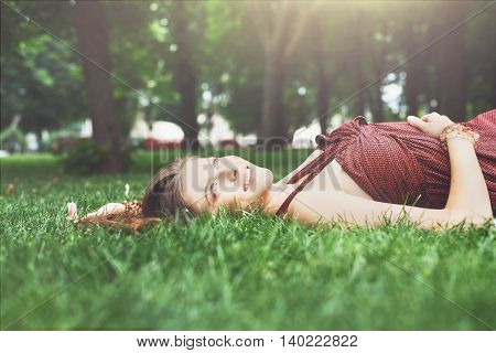 Beautiful young girl lying on grass in summer park, happy and smiling. Female teenager relax outdoors at sunny day. Attractive pretty woman dreaming, looking up