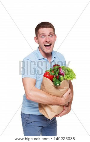 Excited young man holding shopping bags full of groceries isolated at white background. Healthy food shopping. Paper package with vegetables and fruits, happy male buyer came from market