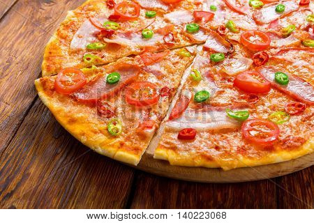 Delicious italian pizza with red and green hot chili peppers, bacon and cherry tomatoes - thin pastry crust at wooden background, one piece cut, closeup