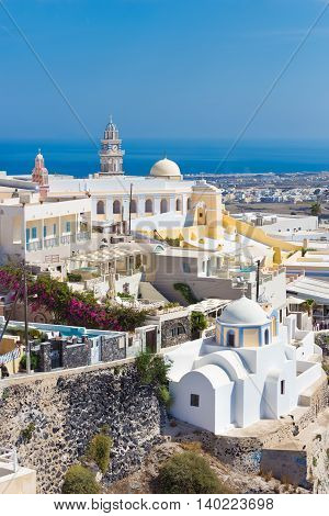 Cityscape of Fira, dramatically located on the edge of the caldera cliff on the island of Thira known as Santorini, Greece. Panorama shot.