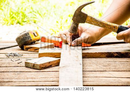 Background Craftsman tool old hammer with tape measure and small nails and saw and working outdoor view.Background for carpenter and repair and craft country style.12
