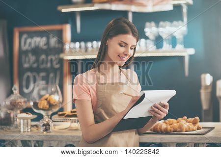Not to forget. Thoughtful smiling and positive female waitress making notes with different kind of sweets in a background being in a modern cafe