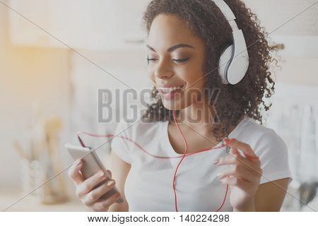 Positive one. Happy and cheerful young woman enjoying her music and holding her phone