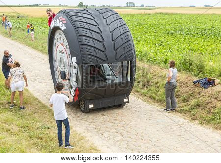 QuievyFrance - July 07 2015: Kleber vehicle during the passing of the Publicity Caravan on a cobblestoned road in the stage 4 of Le Tour de France on July 7 2015 in Quievy France. Kleber is a famous European company which products a wide range of tires.