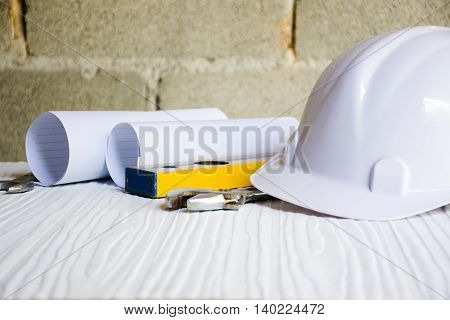 Background for architect and Craftsman tool with paper and cap on white table and background cement wall.