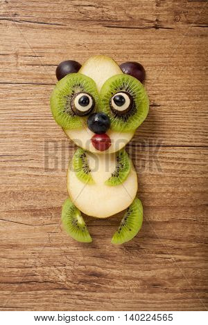 Panda made of pear on wooden background