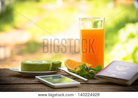 Background fruit and juice with green tea cake and mint with smartphone and passport.All screen for travel and .On wooden background outdoor view and holiday with relax .