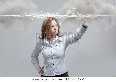 Woman making magic effect - flash lightning. The concept of electricity, high energy.