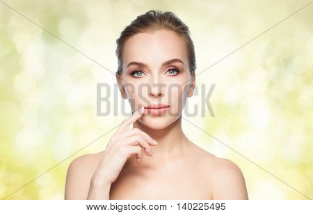 beauty, people and plastic surgery concept - beautiful young woman showing her lips over yellow holidays lights background