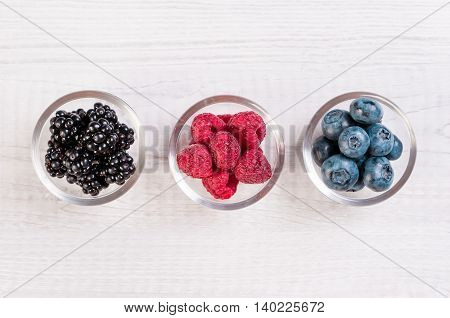 Assorted berries in glass bowls on wood: blueberry, BlackBerry, raspberry