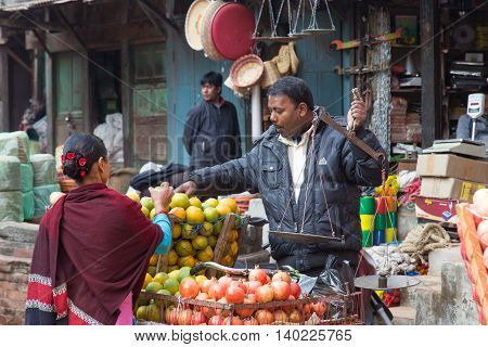 Bhaktapur, Nepal - December 5, 2014: Fruit seller with a customer in the streets.
