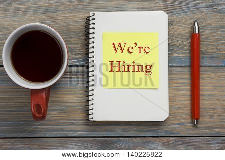 We are Hiring. Office desk table with notepad, pencil and coffe cup. Top view