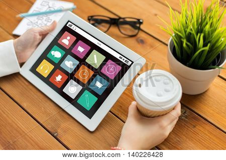 business, media, technology, people and advertisement concept - close up of woman with menu icons on screen on tablet pc computer screen and coffee cup on wooden table