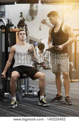 sport, fitness, equipment, lifestyle and people concept - man exercising on gym machine
