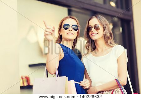 sale, consumerism and people concept - happy young women with shopping bags pointing finger at shop window in city