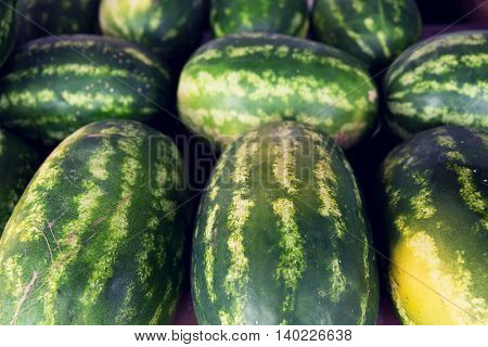 sale, harvest, food, fruits and agriculture concept - close up of watermelon at street farmers market