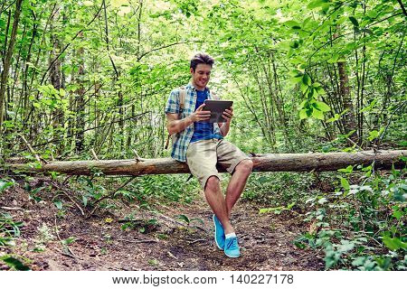 adventure, travel, tourism, hike and people concept - happy young man with backpack and tablet pc computer sitting on fallen tree trunk in woods