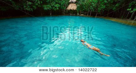 Young woman swimming alone in a blue clear water of a lake situated in tropical forest