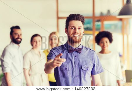 business, startup, people, gesture and teamwork concept - happy young man with beard and bow tie pointing finger at you over creative team in office