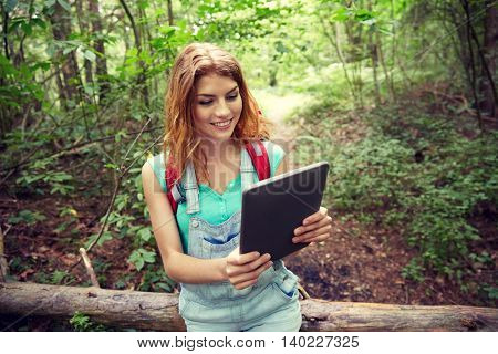 adventure, travel, tourism, hike and people concept - happy young woman with backpack and tablet pc computer sitting on fallen tree trunk in woods