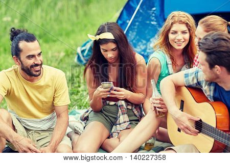 travel, tourism, hike, picnic and people concept - group of happy friends with smartphone and drinks playing guitar at camping