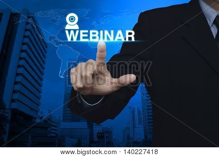 Businessman pressing webinar button over map and city tower Seminar online concept Elements of this image furnished by NASA