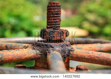 Large rusty valve with thread and nut. An aged and dirty piece of plumbing.