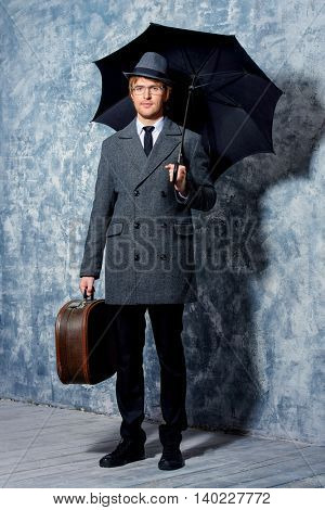 Elegant young man wearing classic hat and a coat stands with his black umbrella. Beauty, fashion.