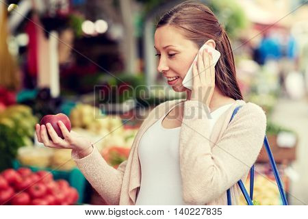 sale, shopping, food, pregnancy and people concept - happy pregnant woman choosing fruits and calling on smartphone at street market