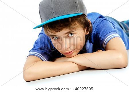 Portrait of a smiling teenage boy lying on a floor. Studio shot. Teen fashion. Isolated over white.
