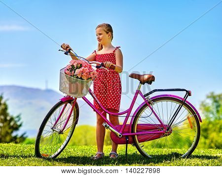 Bicycling girl. Child girl wearing sundress rides bicycle with flowers basket. Mountains and blu sky on background. Good summer weather.