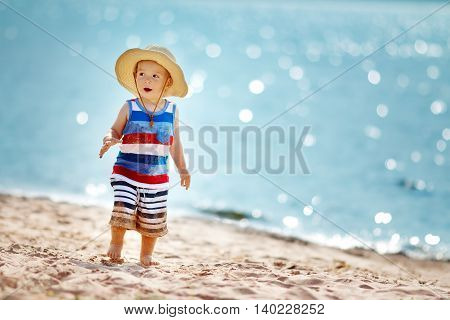one year old boy walking at the beach in straw hat. Child on family vacations at sea