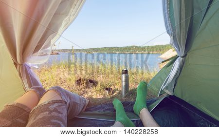 Closeup image couple legs lying together in tourist tent. Light leaks style. Couple on vacation enjoying the beauty of nature. Camping hiking lifestyle.