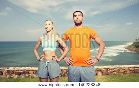 fitness, sport, friendship and healthy lifestyle concept - happy couple exercising over sea or beach background