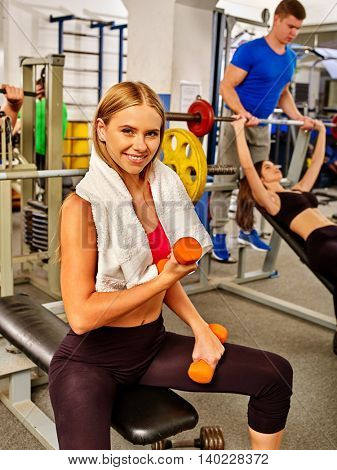 Group of people working with dumbbells his body at gym. Girl with dumbbells in hands into sport gym.
