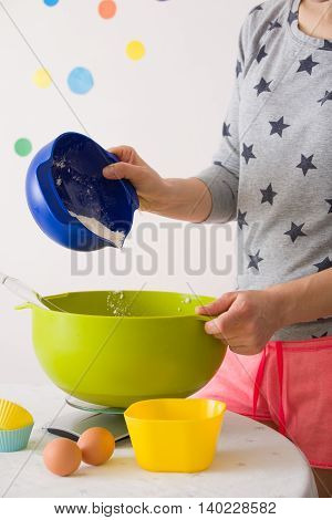 Young woman cooking and home concept - close up of female hands adding flour to the bowl. Preparing homemade muffins and cupcakes. Baking at home. Mixing ingredients for the dough.