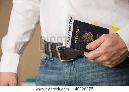 Image of a persons hand holding American passport and ready to travel. Man in a white shirt and jeans holding U.S. passport.