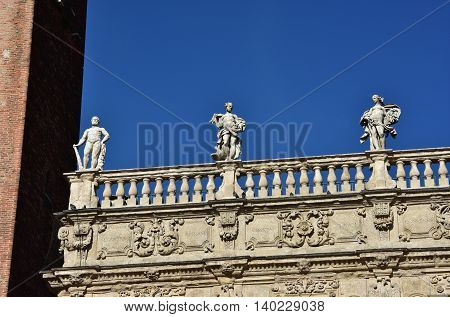 Monumental baroque balustrade of Palazzo Maffei (17th century) with greek gods statues of Jupiter Venus and Hercules in Piazza delle Erbe square in the center of Verona