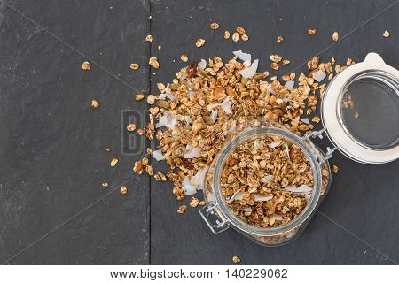 Glass jar of homemade organic granola with coconut and pecans on black background. Delicious breakfast cereal. Healthy muesli.