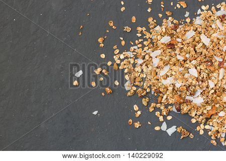 Delicious homemade granola with nuts and coconut flakes on black background. Healthy breakfast cereal. Whole grain.