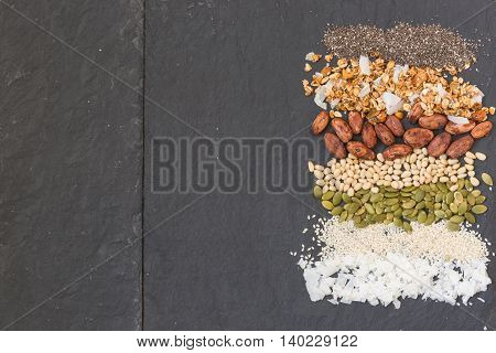 Colorful striped rows of coconut flakes sesame seeds pumpkin seeds cacao beans granola and chia seeds. Mixture of different type of colorful beans and grains.