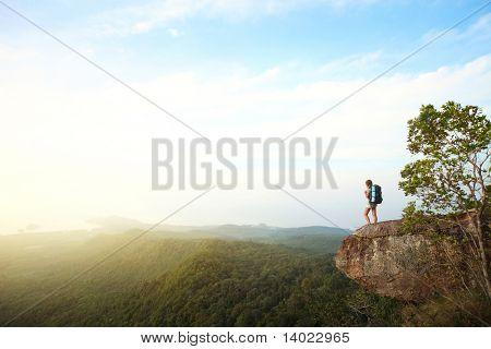 Junge Frau mit Rucksack auf Klippen stehend und auf der Suche zu einem Himmel