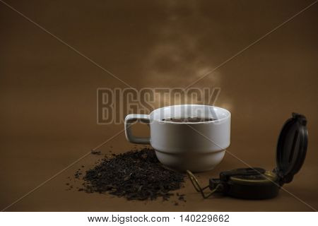 White Tea cup and dry leave tea with compass on brown background.
