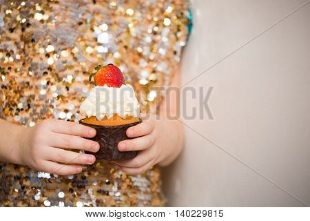 Little girl in a glistening dress holding beautiful cupcake close up. Bakery sweet food and people concept. Delicious muffin on sparkling background. Birthday celebration. Children Party.