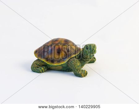 Clay figurine of a crawling turtle on a white background