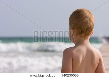2 years old baby boy on the sand beach. Ready to swim. Looking at the waves from the coast.