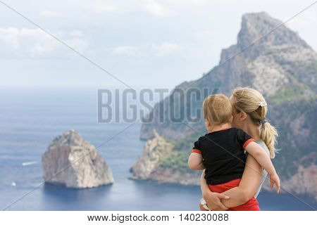 A young mother holding a baby boy and showing him Cape Formentor Mallorca Spain. Sightseeing during vacations in Spain.