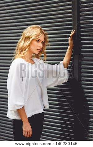 Tired blonde business woman in elegant summer clothing touching black wall outdoors. Split toned photo